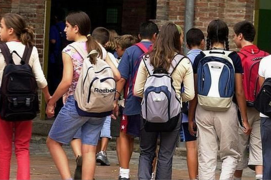 Estudiantes con mochilas, llegando a la escuela