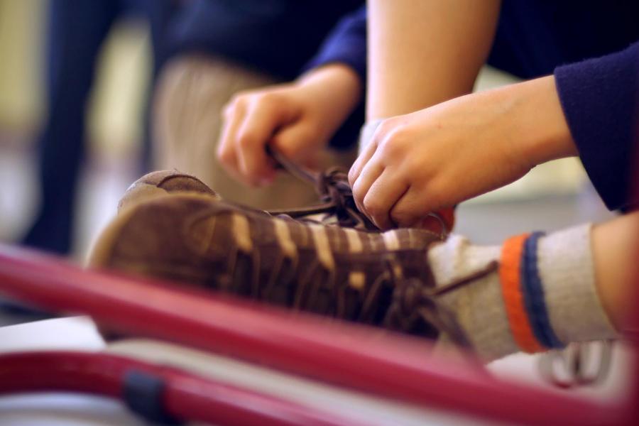 Zapatos de un niño, con sus cordones siendo atados por él
