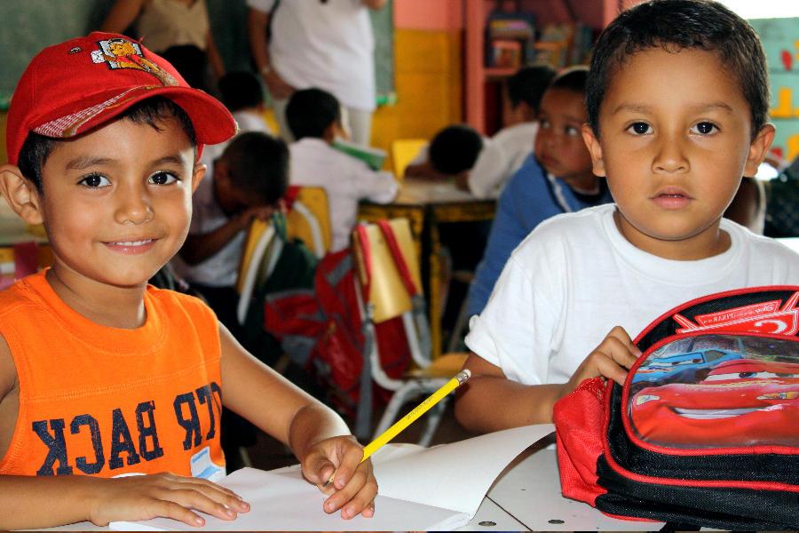 Dos niños dibujando en una hoja