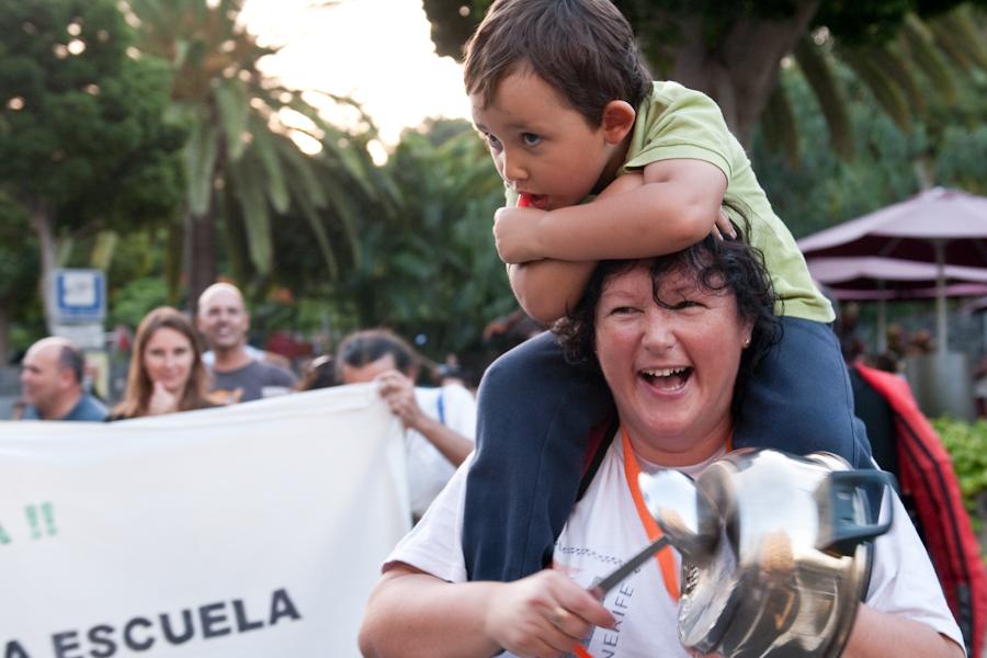 Mujer llevando a un niño pequeño en sus hombros, mientras golpea una cacería