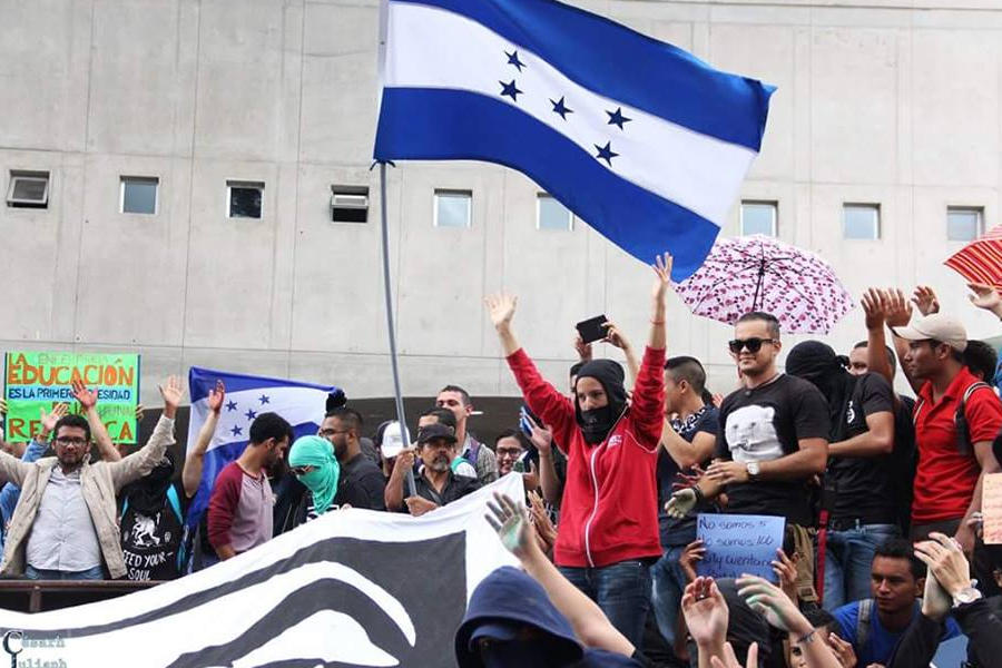 Personas protestan en la calle, con la bandera hondureña
