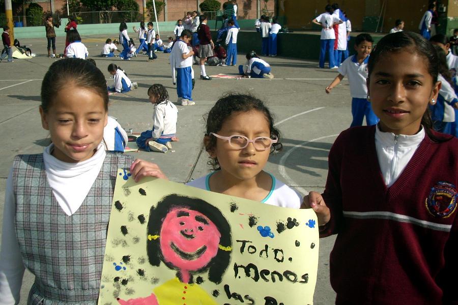 3 niñas colombianas, llevando sus uniformes escolares, sosteniendo una pintura de otra chica
