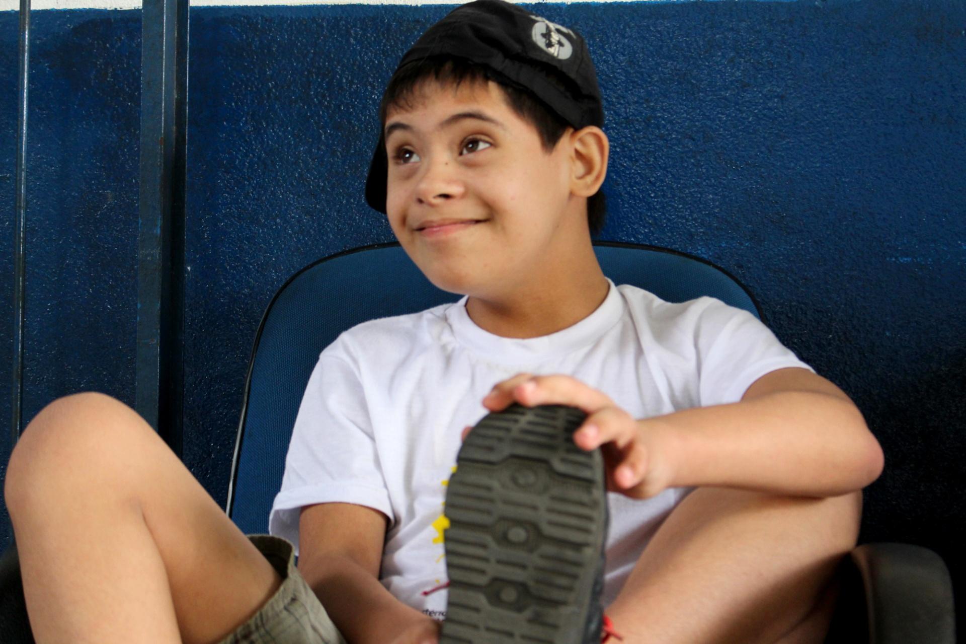 Foto de un niño con síndrome de Down, que está sonriendo y mirando hacia arriba. Él está sentado en una silla azul, frente a una pared también de color azul. El niño lleva una camiseta blanca y pantalones cortos de color gris, así como una gorra negra, girada hacia un lado. Su pie izquierdo está sobre la silla, y él lo agarra con su mano izquierda. Foto: Carlos Palácio