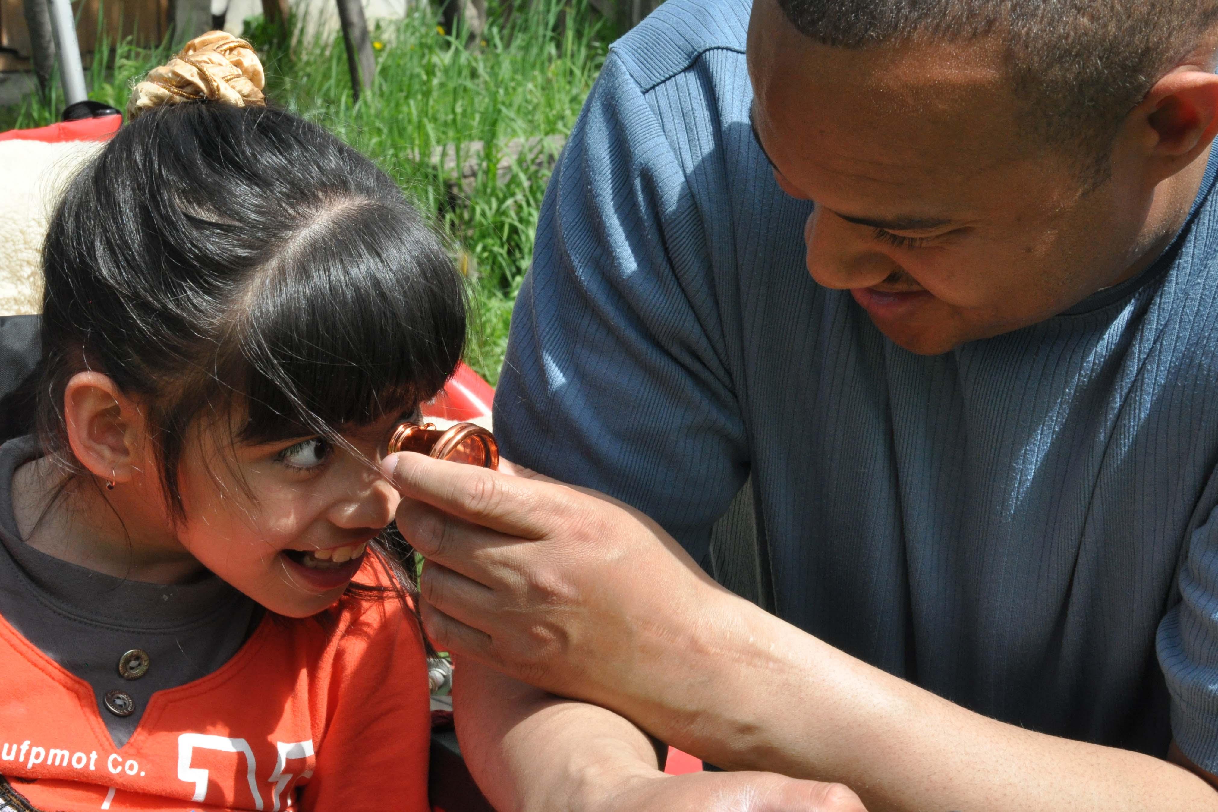 Un hombre negro, con cabello afeitado y llevando una blusa azul, está sentado al lado derecho de una niña en una silla de ruedas, y sostiene  un caleidoscopio en su mano para que ella pueda ver a través del caleidoscopio. La niña tiene pelo negro y flequillo y está sonriendo. Ella lleva una camisa de colores naranja y negro. Foto: Carolyn Viss