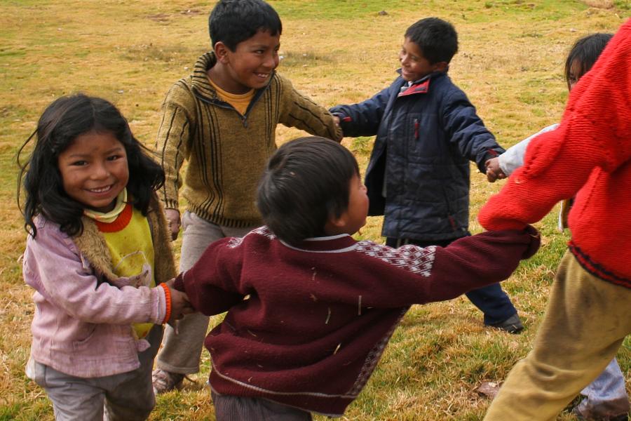Niñas y niños jugando en rueda en un césped