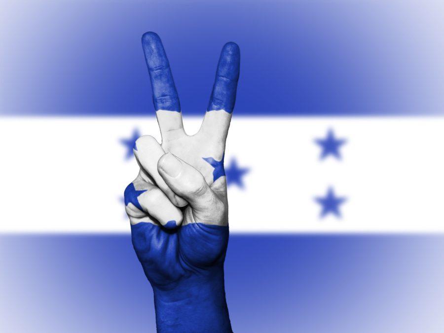 Una mano pintada como la bandera de Honduras, con el dedo índice y el dedo medio levantados, formando el signo de la paz.
