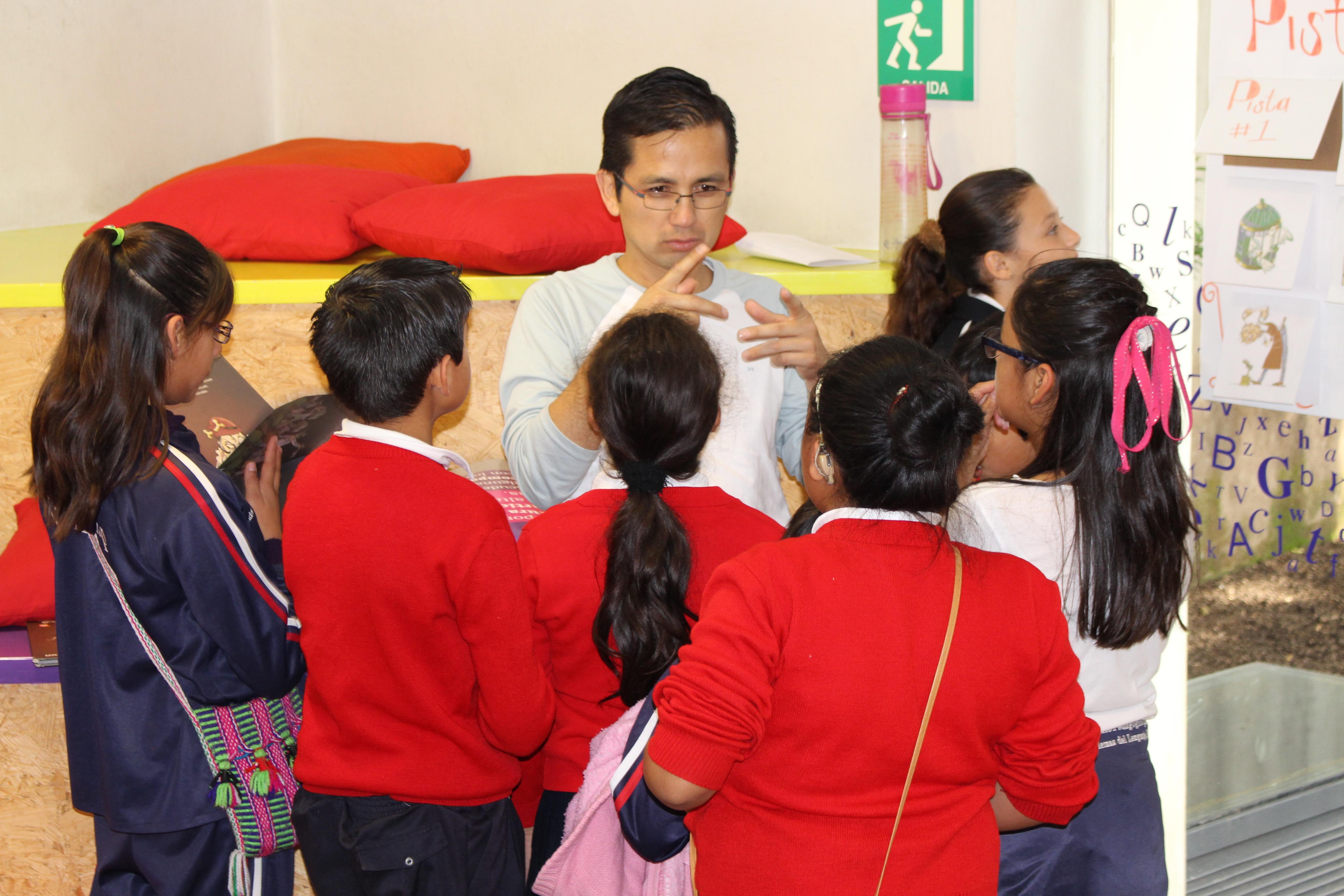 En un aula, un hombre habla, con lenguaje de señas, con un grupo de niñas y niños. El hombre lleva gafas y una blusa gris, y está gesticulando con sus manos. Frente a él y de espaldas para la cámara, están cuatro niñas y un niño. De izquierda a derecha, están: una niña con una cola decballo en el cabello y gafas, lleva una blusa y pantalones de uniforme, los dos de color azul oscuro, y un pequeño bolso tejido en varios colores; un niño con el pelo corto, llevando una blusa roja y pantalones negros; una niña de blusa roja y cabello recogido; una niña con peinado de moño, también llevando una blusa roja, una niña que lleva una camiseta blanca y un lazo rosa en el pelo. Por detrás de ellos, hay otra niña, que está mirando para la derecha. A la izquierda también podemos ver un colchón amarillo y dos almohadas rojas. Foto: Elisa Jarquin