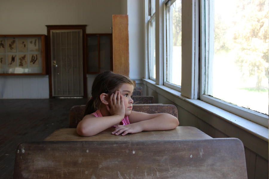 Niña en silla escolar, mirando a través de una ventana