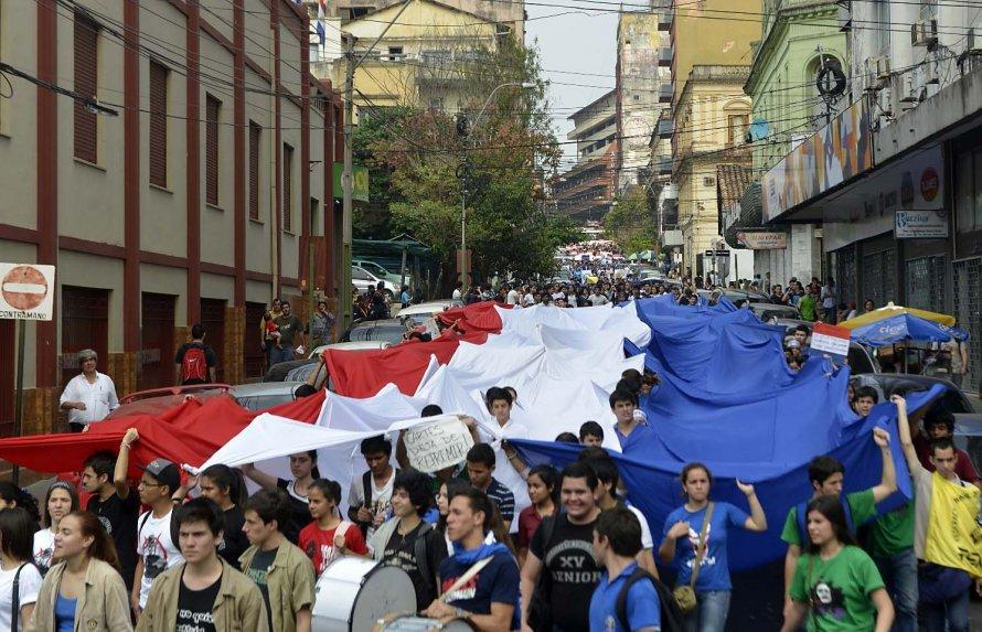 Estudiantes en protesta, llevando una bandera de Paraguay