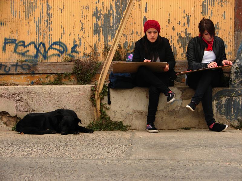 Dos niñas adolescentes escribiendo en un sujetapapeles frente a una pared amarilla. A la izquierda, un perro duerme.