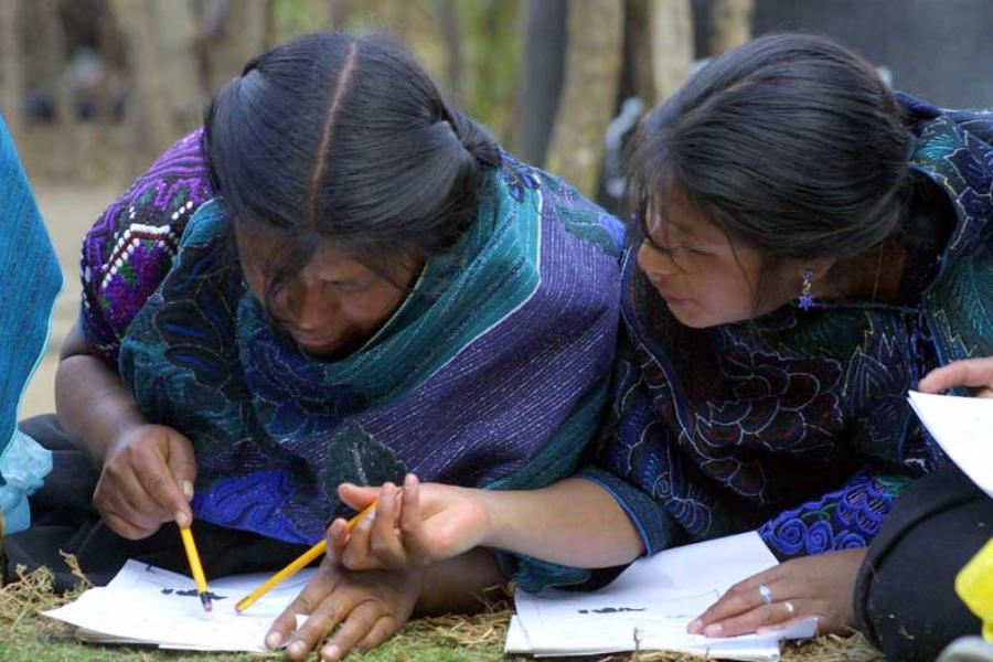 2 mujeres escribindo en una hoja de papel