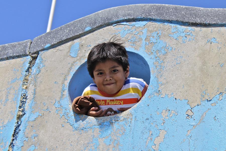 Niño sonriendo, saliendo de una abertura de forma redonda en un muro de concreto, con un cielo azul atrás
