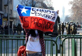 Una estudiante secundarista con la bandera de Chile, donde se lee