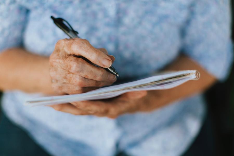 Brazos y manos de una mujer más grande, vestida con una blusa azul, escribiendo en un cuaderno.