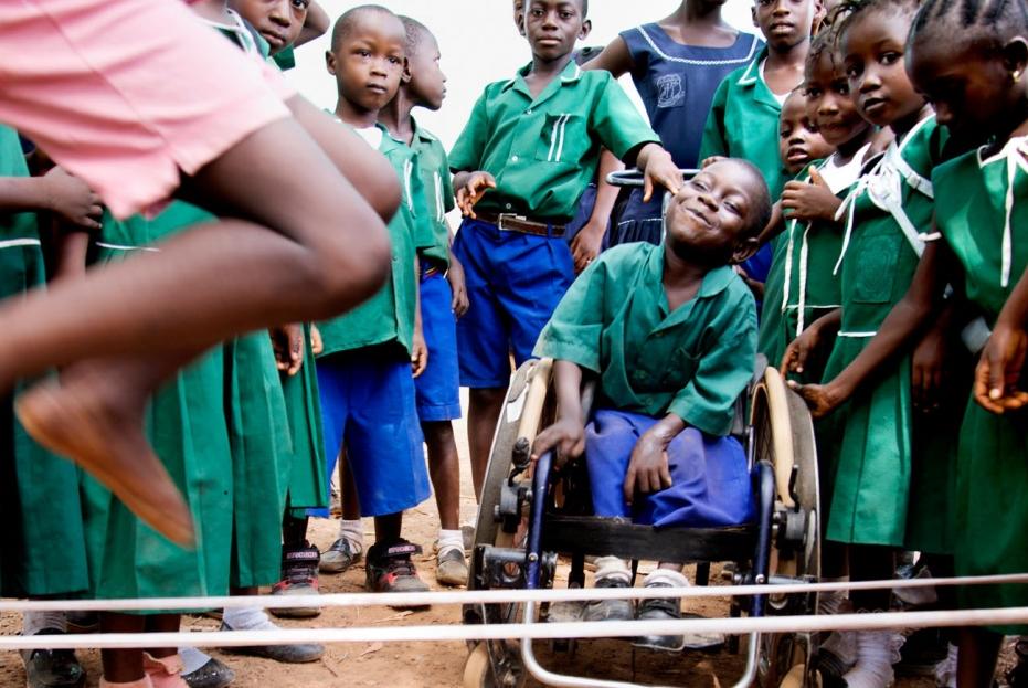 La foto muestra una aglomeración de niñas y niños negros alrededor de un niño en silla de ruedas, ellas y ellos están en la franja de edad entre los 5 y 7 años aproximadamente. Las niñas llevan un uniforme de falda y camisa verde con cuello blanco y los niños llevan un uniforme de camiseta tipo polo de color verde y una bermuda azul rey.