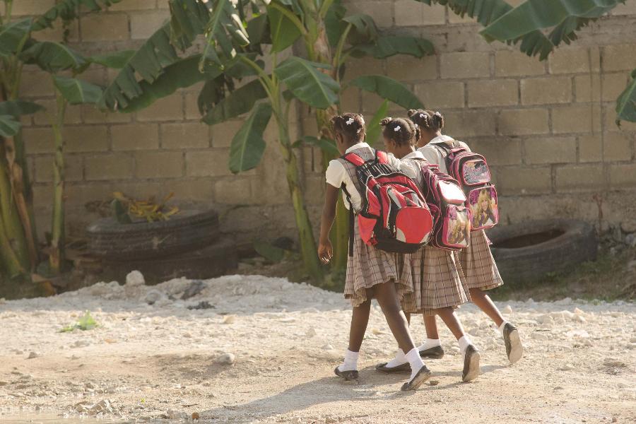 Tres chicas jóvenes que caminan en uniformes escolares haitianos, con mochilas, en un camino sin pavimentar, con algunos árboles de plátano en el fondo