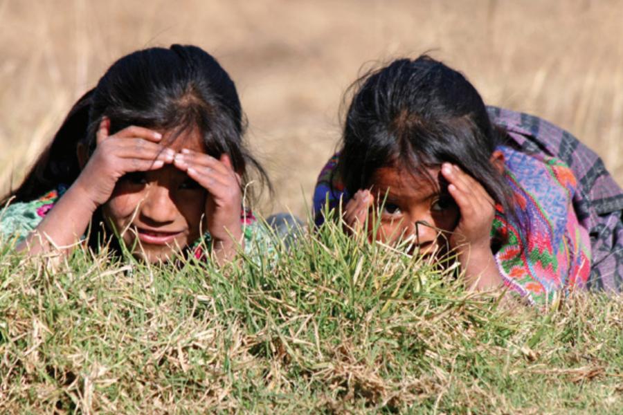 Dos muchachas acostadas boca abajo en la hierba, tapando los ojos con las manos