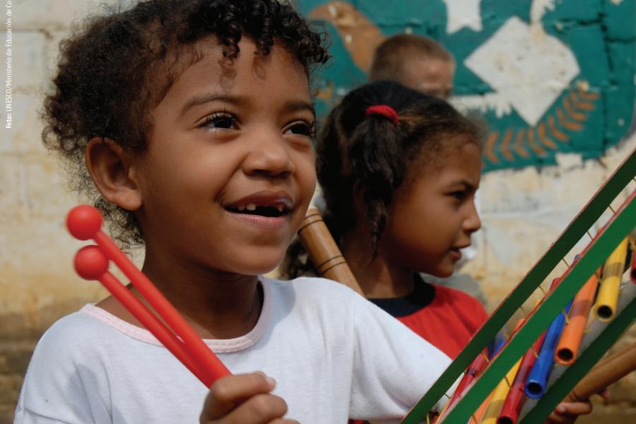 Niño sonriente, en uniforme escolar, tocando el xilófono