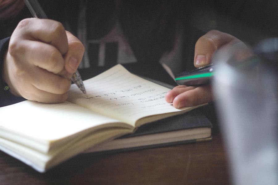 Manos escribiendo en un cuaderno