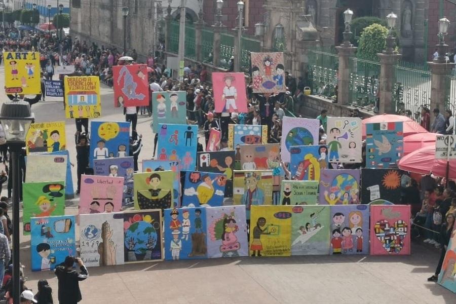 """#ParaQueTodosVean La foto muestra una calle en México, hay un desfile de pancartas realizadas por niños, niñas, jóvenes y adolescentes del país. Las pancartas tienen dibujos y mensajes relativos al derecho a la educación y a los derechos de los niños, niñas y adolescentes. A lado y lado de la calle hay espectadores aglomerados. En el extremo inferior izquierdo de la foto se ve el logotipo de la CLADE, que es un círculo naranja, dentro del cual personas dibujadas en color blanco se dan las manos. En el extremo inferior derecho de la foto, están los créditosde la foto, con el texto: """"Foto: CADEM"""". Fin de la descripción."""