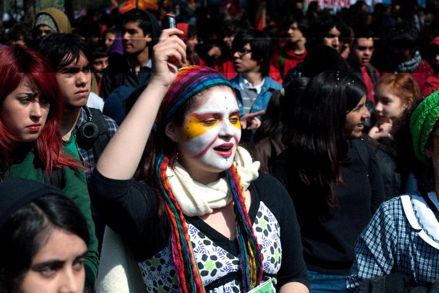 Estudiante en una protesta, con una pintura en la cara