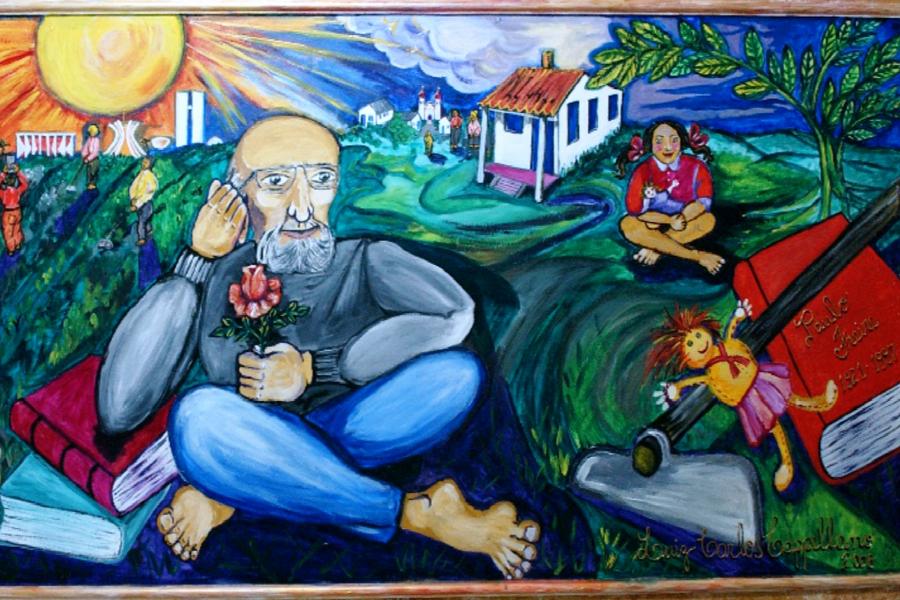 Panel mostrando a Paulo Freire sentado en la hierba con las piernas cruzadas. Detrás de él, una niña juega con una muñeca y, frente a ella, están una azada y un libro.