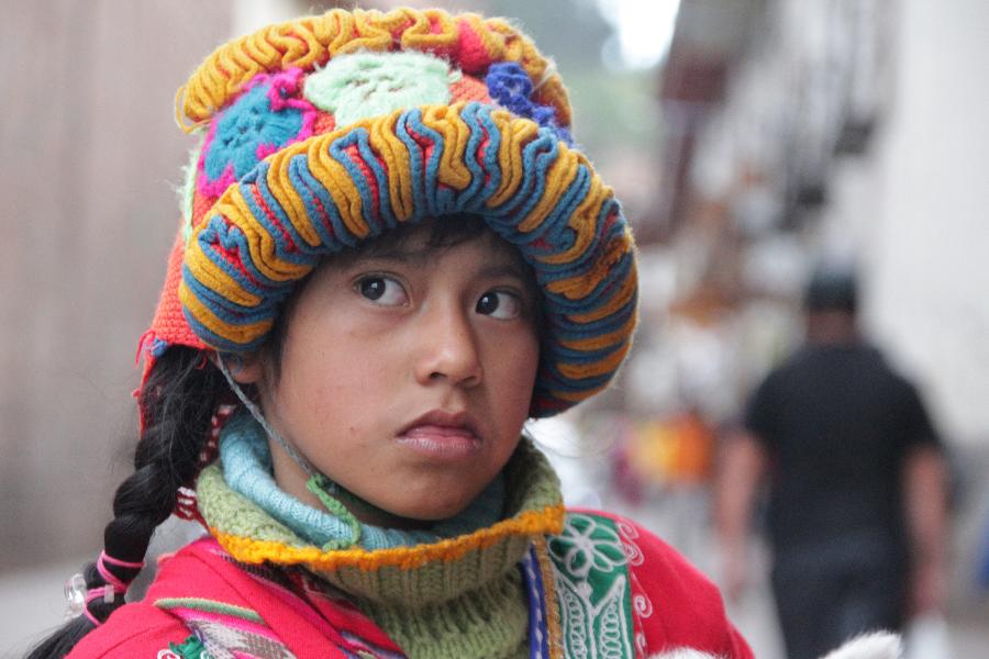 Foto del rostro de una adolescente peruana, mirando a un lado, con un gran sombrero tradicional