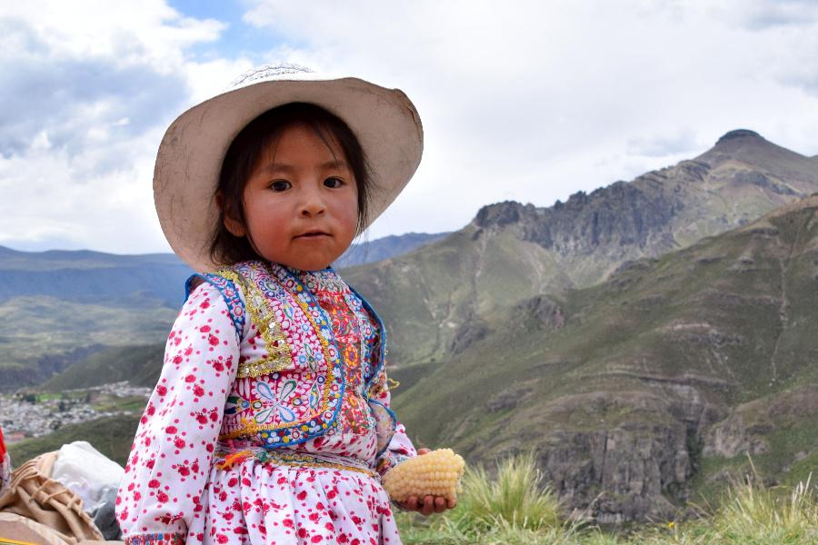 Joven peruana vestida con una camisa rosa de manga larga y un sombrero, sosteniendo un maíz pequeño. En la parte posterior de la imagen, hay montañas y un cielo azul.