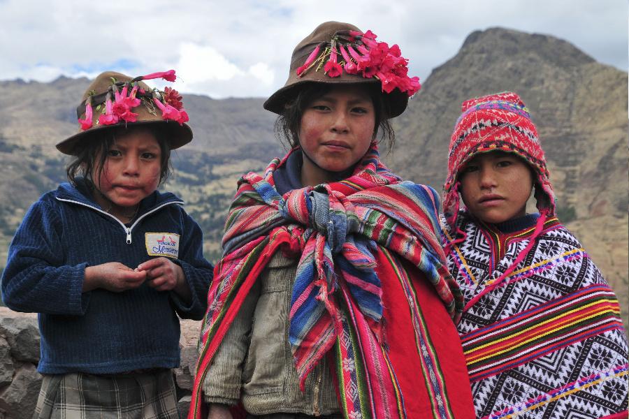 Tres jóvenes peruanas vistiendo indumentaria tradicional. En la parte posterior de la imagen, hay montañas.