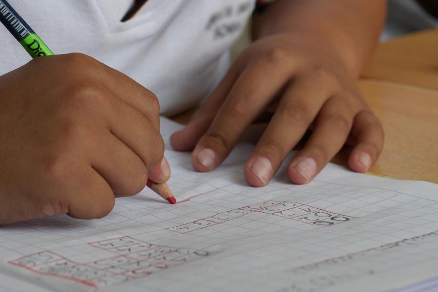 Manos de un niño escribiendo en un cuaderno con un lapís rojo