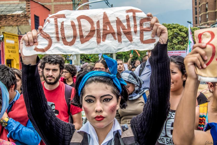 Escena de protesta estudiantil, con una muchacha con maquillaje y un lazo en la cabeza sosteniendo una placa en la que se lee