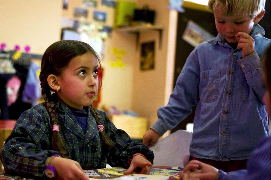 Chica con los pelos trenzados y una chaqueta ajedrez sentada en una mesa mirando hacia arriba, al lado de un niño rubio que está de pie.
