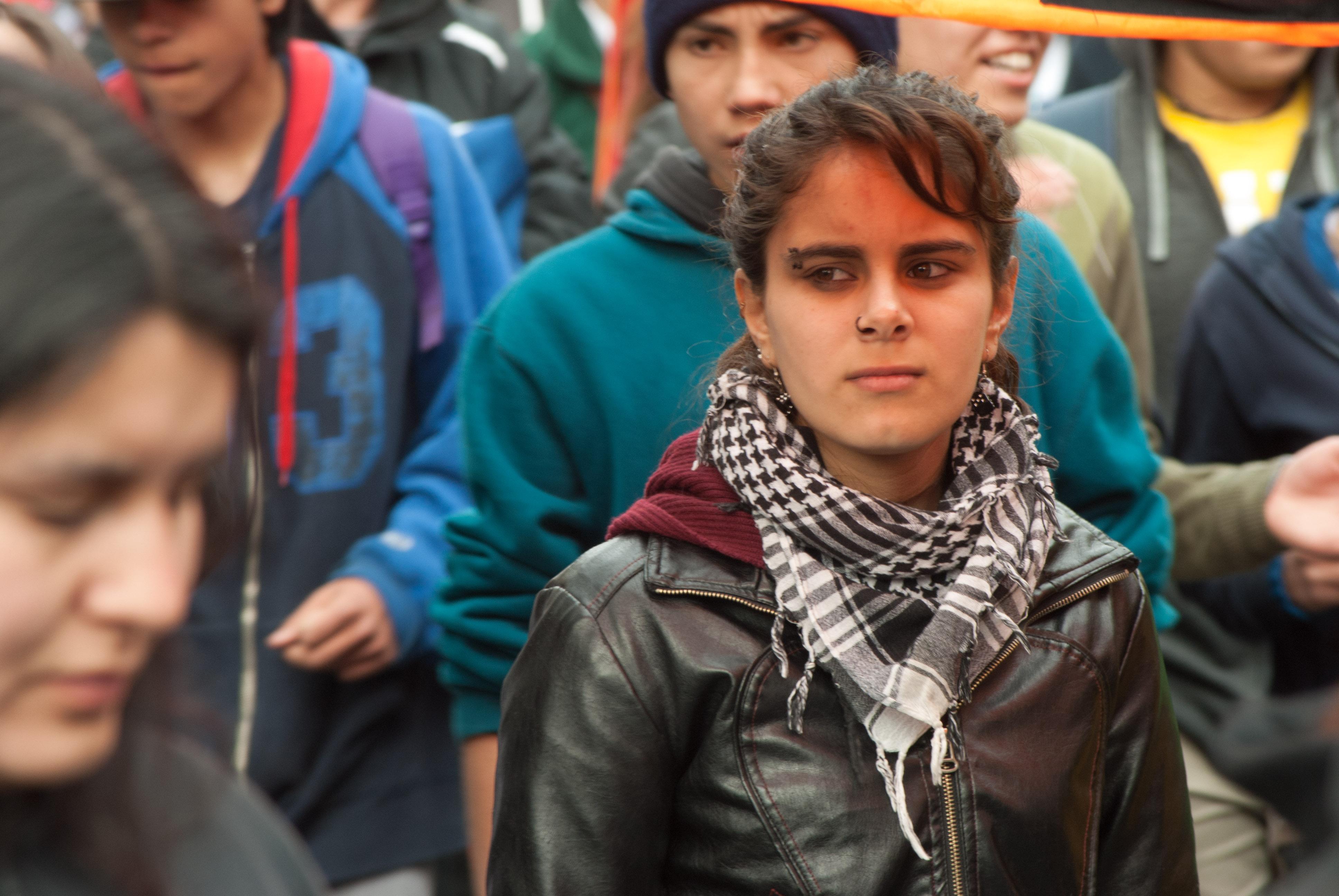 Estudiante en protesta, con una chaqueta de cuero y una bufanda