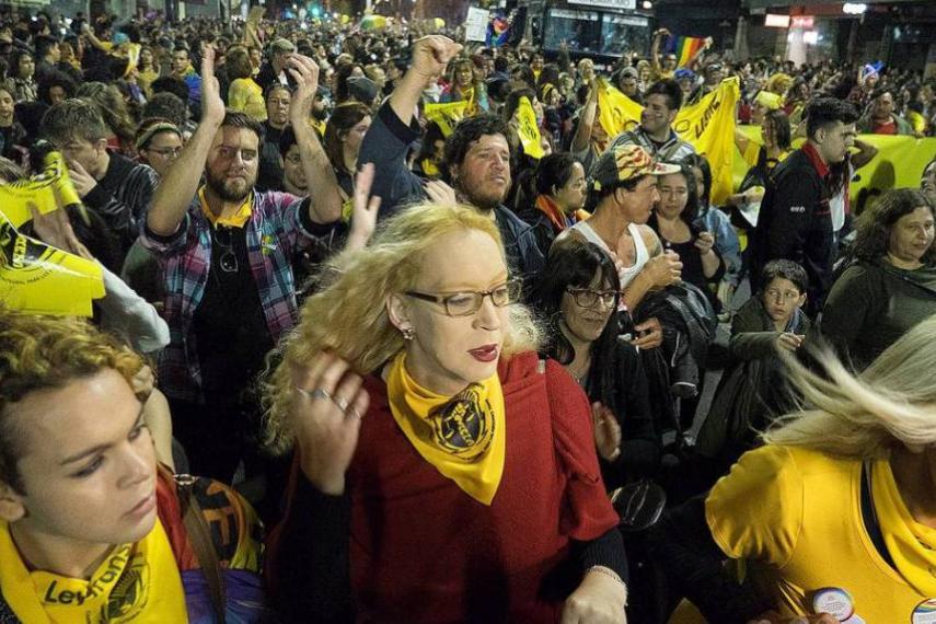 Mujeres trans protestando en la calle, usando un pañuelo amarillo alrededor del cuello