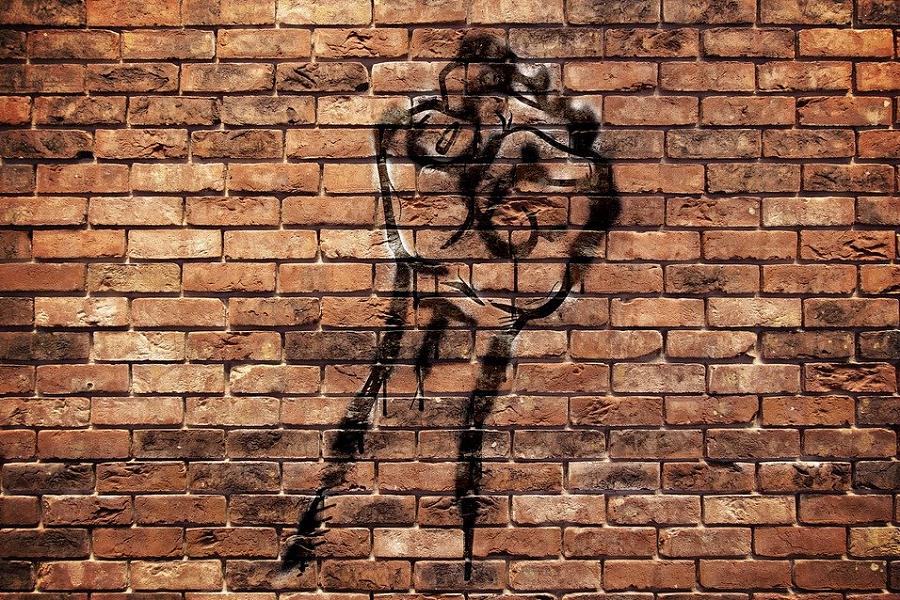 La foto muestra un muro con ladrillos a la vista de color terracota, sobre el muro hay un grafiti con la silueta en negro de una mano en empuñada hacia arriba como símbolo de protesta.
